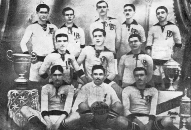 Elenco campeão paulista em 1914 ao lado da taça do primeiro título do Corinthians