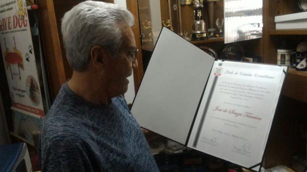 Seu José mostra com orgulho título de cidadão corinthiano da Câmara Municipal de SP